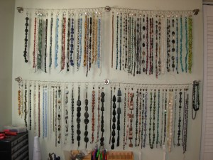 Strands of beads on the Beadphoria studio wall using a tention wire and clips.
